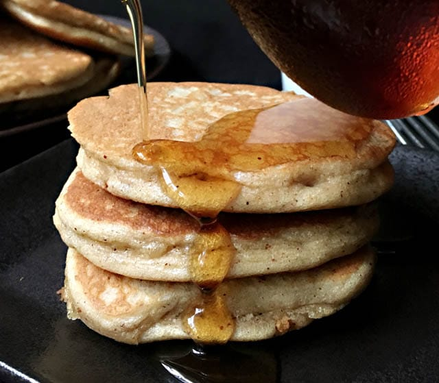 Brown syrup being poured over a stack of 3 brown almond pancakes on a dark plate