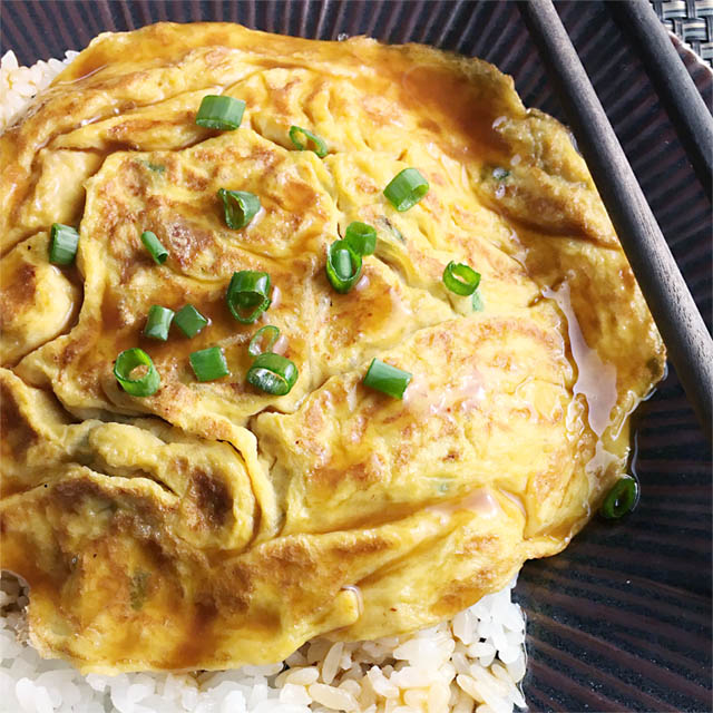 Yellow fried egg foo young omelette topped with chopped green onion on white rice on a dark plate