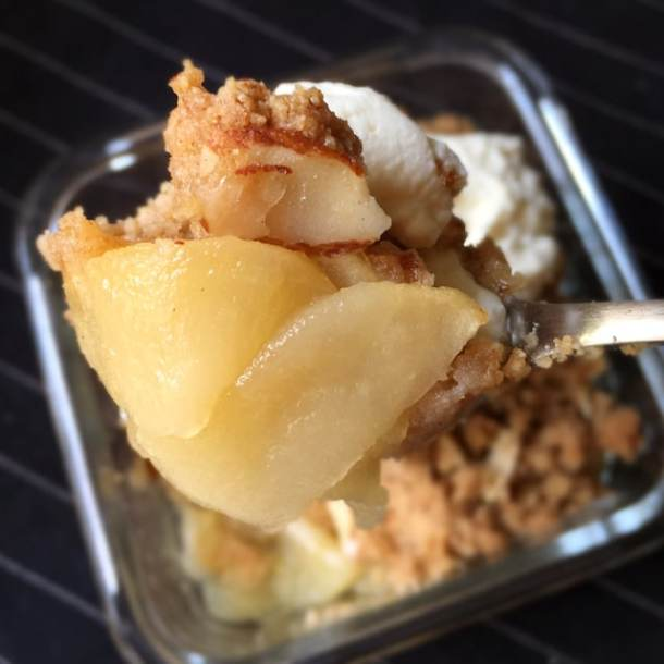 Close-up of a spoonful of yellow cooked apple slices, brown almond crumbs, and white whipped cream
