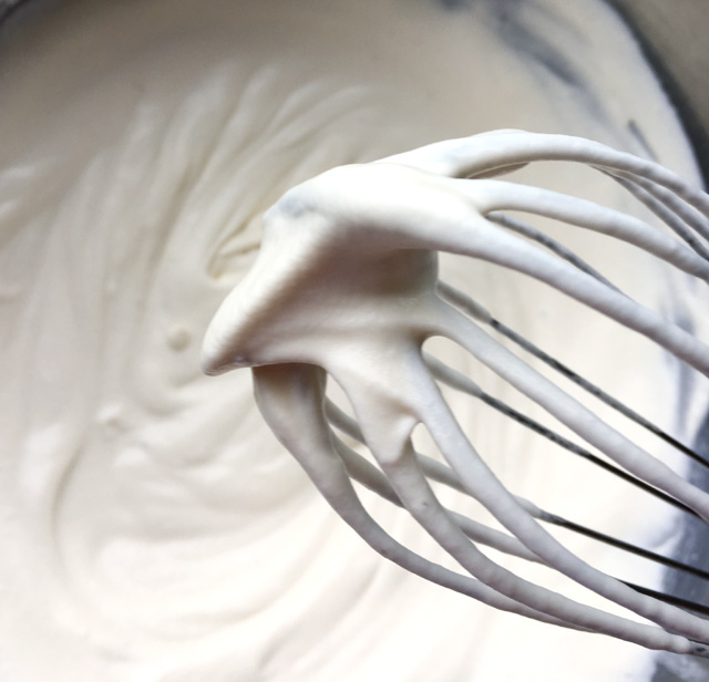 Close-up of a whisk with soft white whipped cream peaks