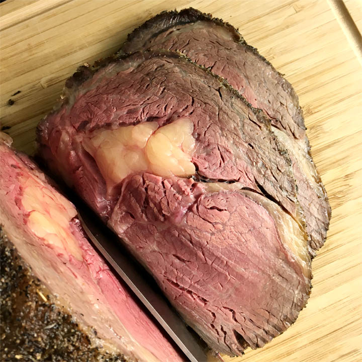 A knife slicing through a beef rib roast, slices of pink and brown beef on a wooden cutting board