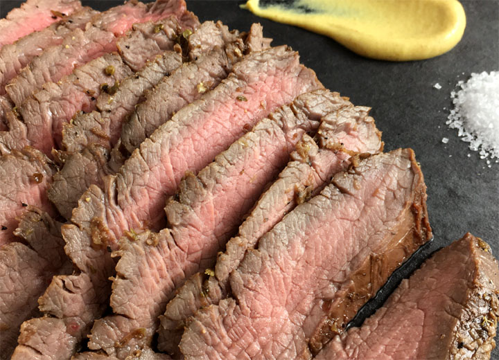 Close-up of sliced steak next to yellow mustard and white salt on a black platter