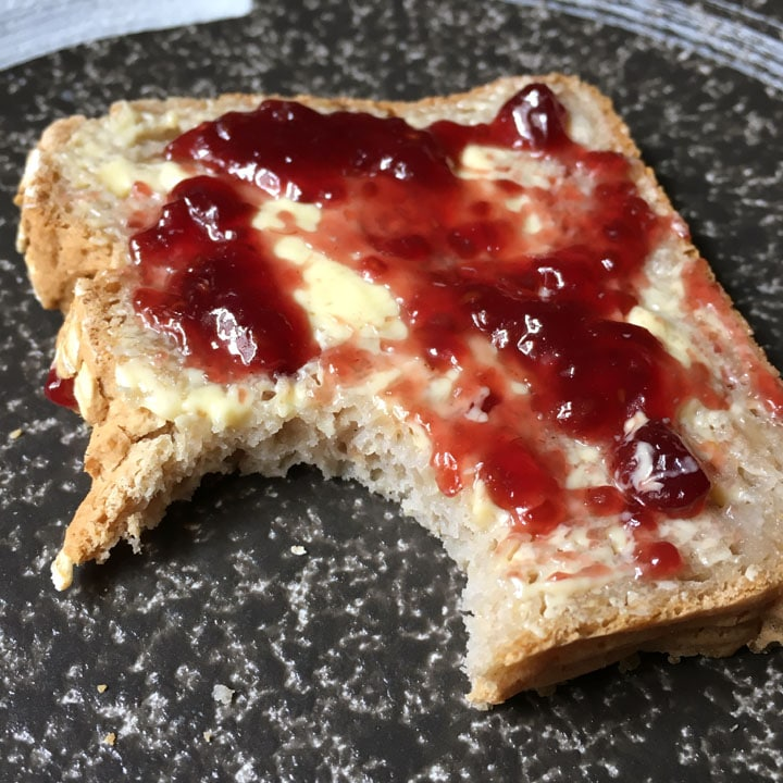 A dark round plate containing a slice of bread with butter and red jam and a bite taken out of it