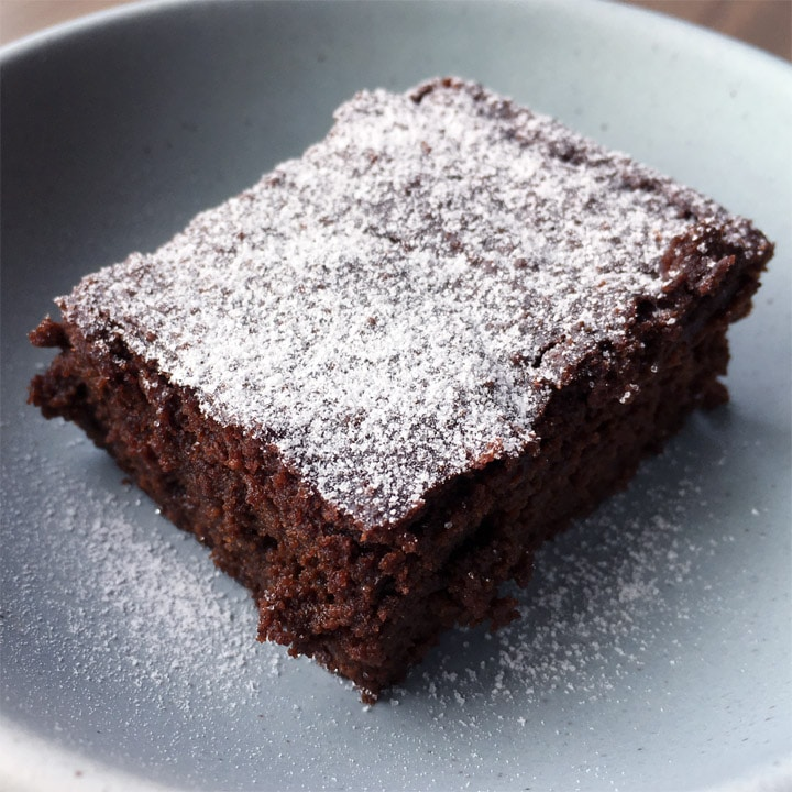 Closeup of a square piece of chocolate cake dusted with white powdered sugar on a round plate