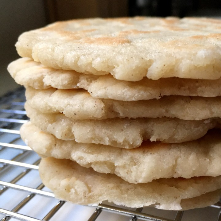 A stack of 6 light brown flatbreads on a metal rack
