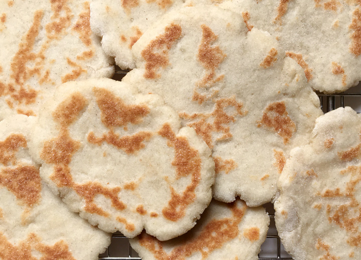 Several round light brown flat breads with dark browned spots