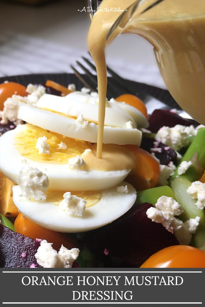 Yellow dressing being poured over a salad, the words orange honey mustard dressing on the bottom