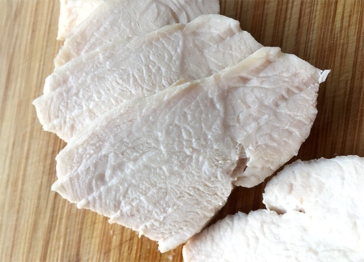 Slices of white chicken meat on a wooden cutting board