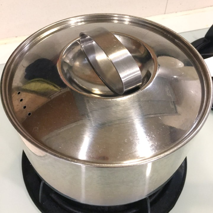 A silver cooking pot with the lid on on a stove