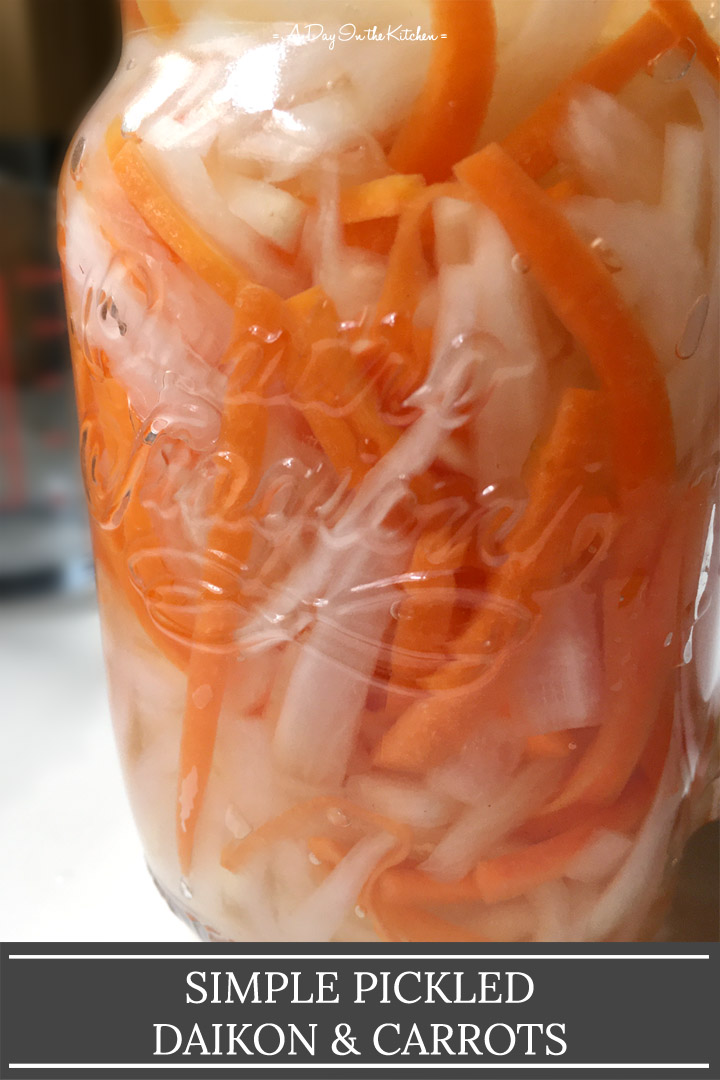 Close-up of a glass jar containing strips of white radish and orange carrot, the words simple pickled daikon and carrots on the bottom