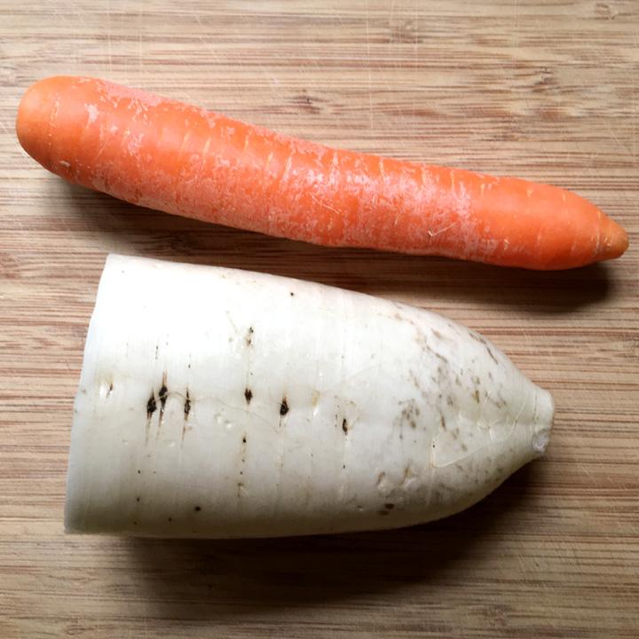 A white daikon radish and an orange carrot on a wooden cutting board