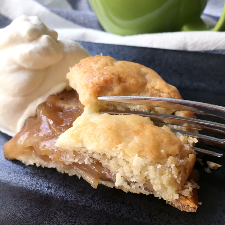 A fork cutting into a wedge shaped piece of apple galette, next to a mound of white whipped cream