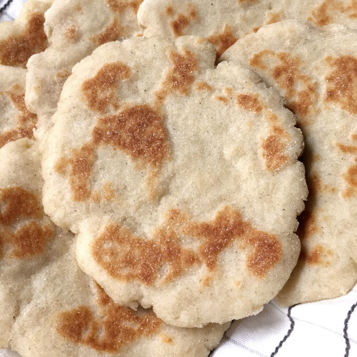 Several round, brown flatbreads on a white towel