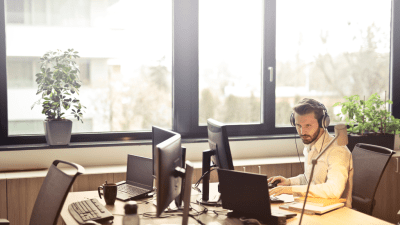 man with ADHD wearing headphones to help avoid distractions as he works