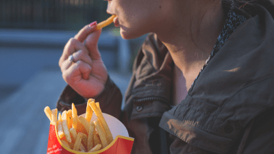 A woman with ADHD impulsively eating french fries