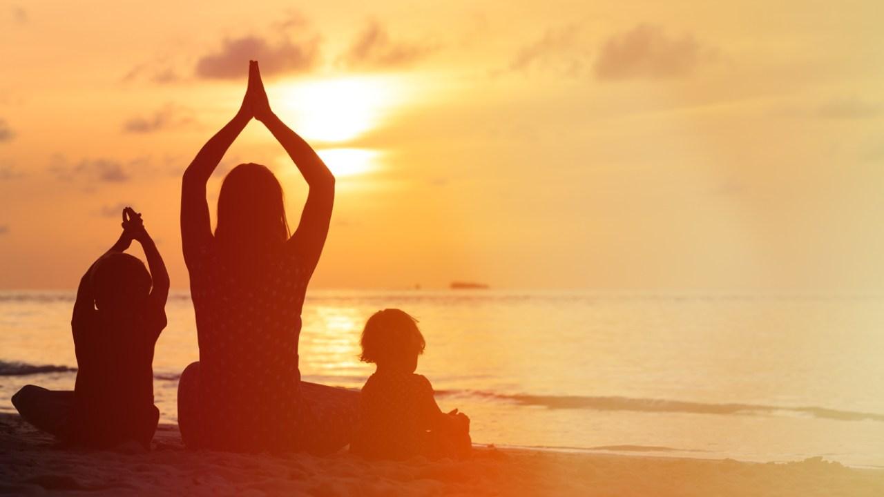 Family doing yoga on the beach