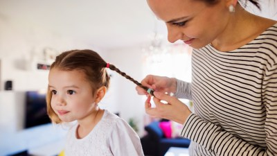 A mom braids her daughter's hair as part of their morning routine