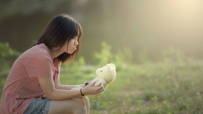 A young girl with anxiety, sitting in a field