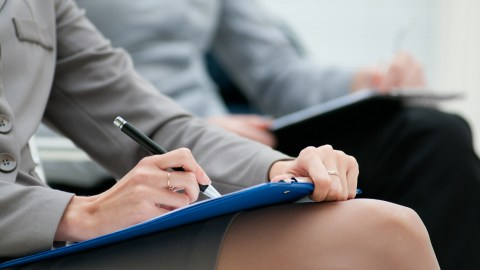 A businesswoman taking notes which allows her to easily recall details later and manage her ADHD in the workplace.