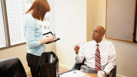 Two workers discussing a project, which allows them to improve efficiency and manage ADHD in the workplace.