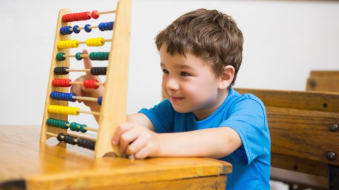A boy doing a good job in class with an abacus, and modelling good behavior for his classmates, a great way to improve classroom behavior.