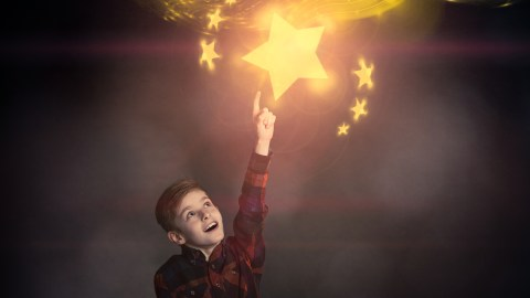 A child reaches for the moon as an example of a reward system for kids that works.