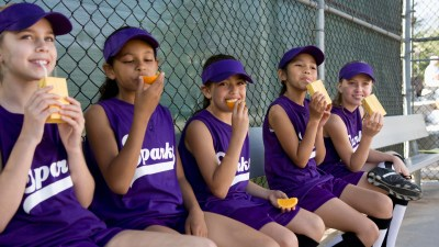 A group of girls learn how to make friends by playing softball together
