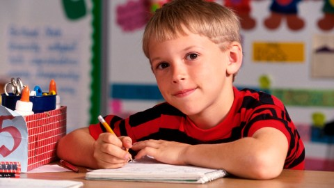 A child smiles in class as he practices ADHD writing strategies