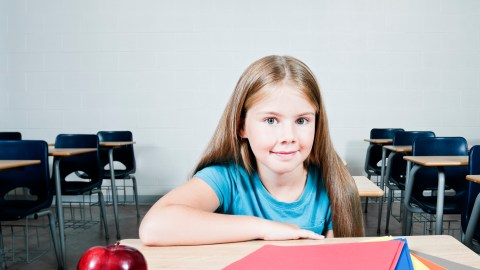 A girl with ADHD uses color-coded folders to keep her schoolwork and desk organized.