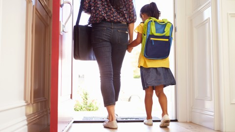 A mom and her daughter with ADHD walk out the door to go to school.