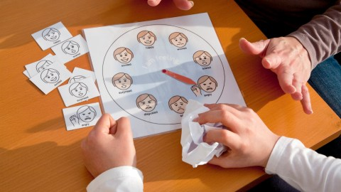 A child looks at an emotion wheel. A therapist tries to determine if the child has ADHD or autism.
