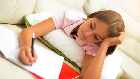 A girl uses ADHD homework strategies to finish her assignments