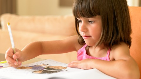 A girl uses ADHD homework strategies to finish her assignments.