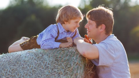 A father talks to his son about anger management while he lays on a hay bale.