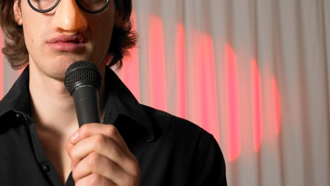 A comedian wears a fake nose and glasses on stage, and finds humor in ADHD symptoms.