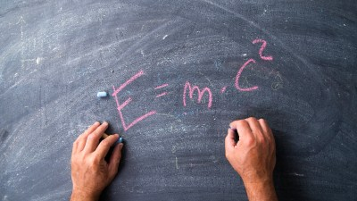 A child who is twice-exceptional writing out E=MC2 on a blackboard in pink chalk