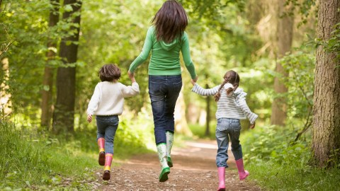 Mother and daughters skip through the woods, taking a walk on the wild side.