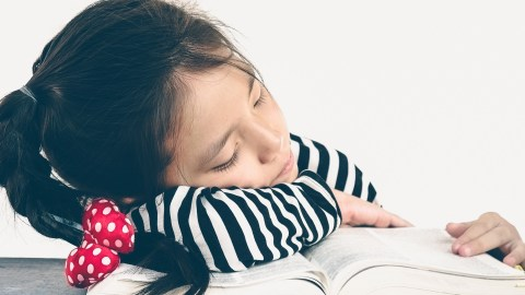 A girl taking a nap on her textbook, since short naps can help children with ADHD study more effectively