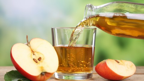 Apple juice being poured into a glass; sugary drinks can help kids with ADHD learn how to study better