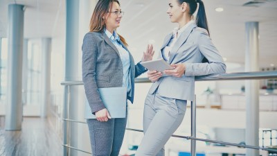 A woman discusses strategies to succeed with ADHD at work with a colleague.