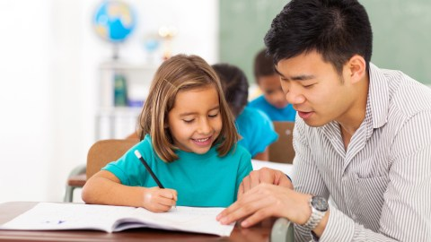 A teacher checking the student's school planner, which is an excellent way to ensure quality communication.