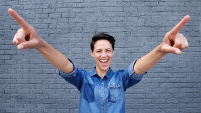 A woman pointing her fingers excitedly after learning how to raise her self-esteem