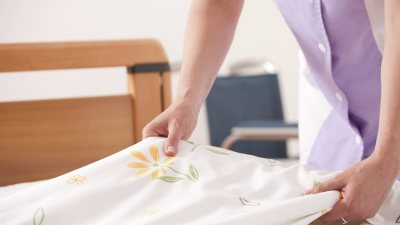 A woman folding white sheets on a bed, no longer overwhelmed by clutter