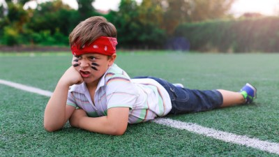 Boy with ADHD and Oppositional Defiant Disorder ODD laying on rugby field with face paint on making angry face