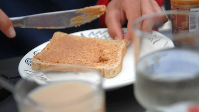 ADHD child smears peanut butter on toast