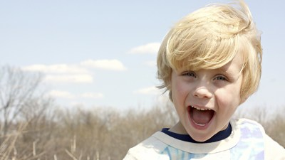 Boy with ADHD laughing outside on sunny day after taking his Ritalin