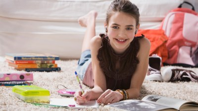 Girl with ADHD doing homework on carpet with books.