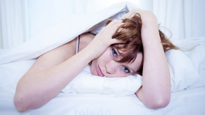 Woman with ADHD in bed, unable to sleep and holding head, with frustrated expression