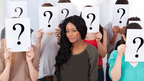 Student Surrounded By Classmates Holding Question Mark Signs