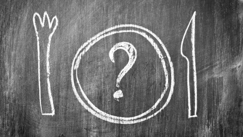 A drawing on a chalkboard of a plate with a question mark, a fork, and knife, a reminder to plan what to have for dinner